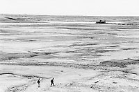 Kazakhstan. Aralsk. Two children walk in the Aral sea. Due to the man-made environmental disaster by overuse of water resources and the environmental effects of industrial pollution in the former Soviet Union, the Aral sea started to dry up, then shrunk and is now two shallow lakes far from the old shore (100 km distant). Aralsk is located in the Kyzyl Orda Province. © 2008 Didier Ruef . ..