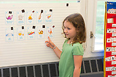 MR / Schenectady, NY. Zoller Elementary School (urban public school). Kindergarten classroom. Student (girl, 5, native Spanish speaker) points to vocabulary word card during Spanish lesson for bilingual students. MR: Cas12. ID: AM-gKw. © Ellen B. Senisi.
