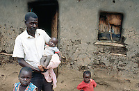 Kenya. Rift Valley Province. Matisi. A father holds in his arms his youngest daughter. The man and two more of his children stand in front of the door of their poor mud hut.  © 2004 Didier Ruef