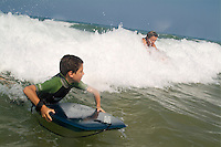 Young boy and his mother surfing waves together at Le Porge beach, Bordeaux, France.