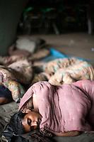 Homeless rickshaw wallahs sleep beneath a bridge at dawn near the banks of the Yamuna River.