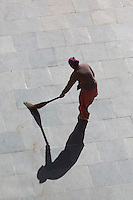 Sweeping the courtyard at Thiksey Monastery near Leh, Ladakh