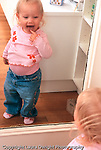 18 month old toddler girl recognizing self in mirror touching own tongue vertical Caucasian