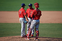 Williamsport Crosscutters pitching coach Hector Berrios (21) talks with pitcher Orestes Melendez (17) and catcher Nerluis Martinez (11) during a mound visit during the second game of a doubleheader against the Batavia Muckdogs on August 20, 2017 at Dwyer Stadium in Batavia, New York.  Batavia defeated Williamsport 4-3.  (Mike Janes/Four Seam Images)