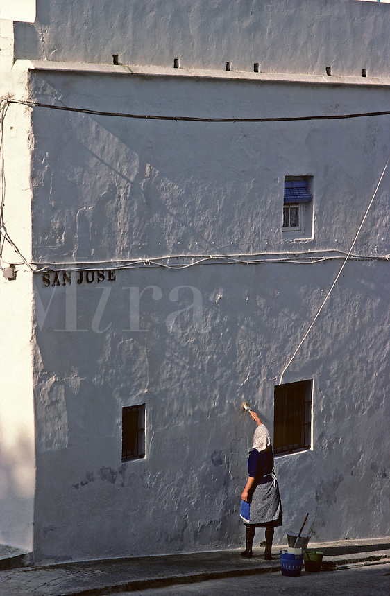 Spain. Medina Sidonia.  Woman whitewashing the wall of her typical house in small Spanish town.  Near Cadiz..