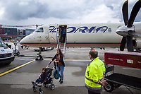 "Switzerland. Canton Ticino. Zurich Airport  An Adria Airways Saab 2000 on the airport tarmac. Two passengers, a mother and her child seated in a baby stroller, walk towards the bus. The Adria Airways company works on behalf of Swiss for a connecting flight from Lugano to Zürich. Swiss International Air Lines AG (stylised as SWISS), commonly referred to as Swiss, is the national airline of Switzerland. The Saab 2000 is a twin-engined high-speed turboprop airliner built by Saab. It is designed to carry 50–58 passengers and cruise at a speed of 665 km/h. Zurich Airport (German: Flughafen Zürich, IATA: ZRH, ICAO: LSZH), also known as Kloten Airport, is the largest international airport of Switzerland. The tarmac  is also often used to describe airport aprons (also referred to as ""ramps""), taxiways, and runways regardless of the surface. 29.05.2019 © 2019 Didier Ruef"
