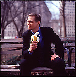 Out of focus man in suit sitting on park bench holding a banana