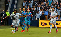 KANSAS CITY, KS - MAY 29: Gianluca Busio #10 of Sporting KC and Maximiliano Urruti #37 of Houston Dynamo FC battle for the ball in midfield during a game between Houston Dynamo and Sporting Kansas City at Children's Mercy Park on May 29, 2021 in Kansas City, Kansas.