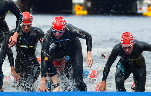 17 JUL 2011 - HAMBURG, GER - Competitors scramble up the ramp  at the end of the first swim lap during the women's Hamburg round of triathlon's ITU World Championship Series .(PHOTO (C) NIGEL FARROW)