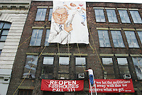 Artist Scott LoBaido secures a mural next to Engine 212 in Brooklyn, NY on August 21, 2003 in protest of mayor Michael Bloomberg's decision to close several firehouses throughout the city.