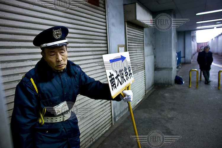 An elderly man works as a security guard, holding a sign for a funeral home in Kamagasaki. Once a thriving day labourer's town in Osaka, Kamagasaki today is home to about 25,000 mainly elderly day labourers, with an estimated 1,300 who are homeless. Alcoholism, poverty and suicide are common in these towns.