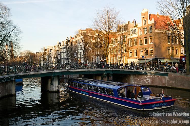 A canal boat sails under a bridge in Amsterdam.