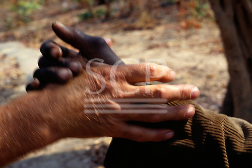 Mbala, Zambia. Black and white hands; shaking hands.