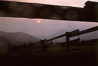 Sunny smoke filled landscape with split rail fence