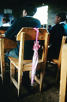 Kenya. Rift Valley Province. Nyahururu. Classroom at Munyaka secondary school. Students, girls and boys, listen to their teacher's lesson. The pupils are wearing a green uniform. A pink umbrella is on a wood chair. © 2004 Didier Ruef