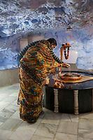 India, Dehradun.  Man and Woman Offering Coconut Milk Libation to   Sheshnag, the Divine Five-headed Serpent in Hindu Mythology, at Tapkeshwar Hindu Temple.