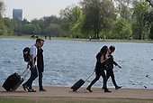 Tourists with wheelie suitcases, Kensington Gardens, London.