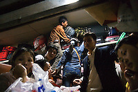 Textile workers carrying their possessions squeeze into a train as they head home to celebrate Chinese New Year.