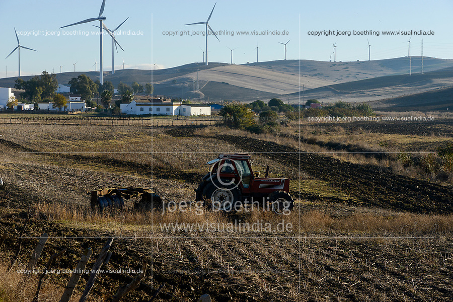 Spain, Andalusia, Cadiz, village La Zarzuela, wind farm in the mountains, Fiat tractor ploughing field