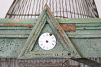Chateau de Lascaux, Vacquieres village. Pic St Loup. Languedoc. An old wooden and iron wire bird cage with a clock without dials. France. Europe.