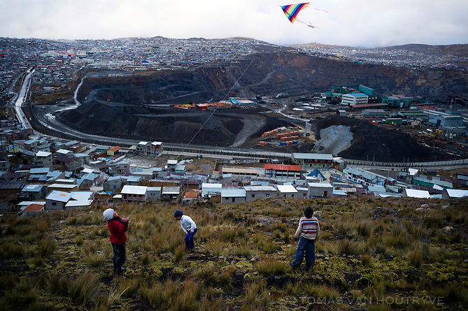 Children, including Yaro Castro Luciano, 13, red shirt, Admer Jordan Tolentino Ayala, 9, striped shirt, Yan Tolentino Ayala, purple shirt, and Anthony Nerio Deudor Torochea, 7, white shirt, flight kites on a hill above the Jose Carlos Mariategui neighborhood of Cerro de Pasco, Peru. In the background, in the center of the city, is the open-pit mine operated by Volcan.