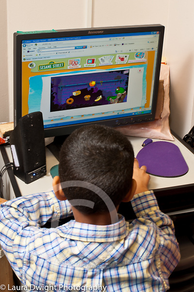 Education Preschool boy playing game on desktop computer in classroom