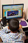 Education Preschool boy playing game on desktop computer in classroom