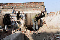 A worker demolishes a wall in a tannery in the city of Kanpur.