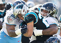 CHARLOTTE, NC - NOVEMBER 3: Christian McCaffrey #22 of the Carolina Panthers is tackled by Jeffery Simmons #98 and DaQuan Jones #90 of the Tennessee Titans during a game between Tennessee Titans and Carolina Panthers at Bank of America Stadium on November 3, 2019 in Charlotte, North Carolina.