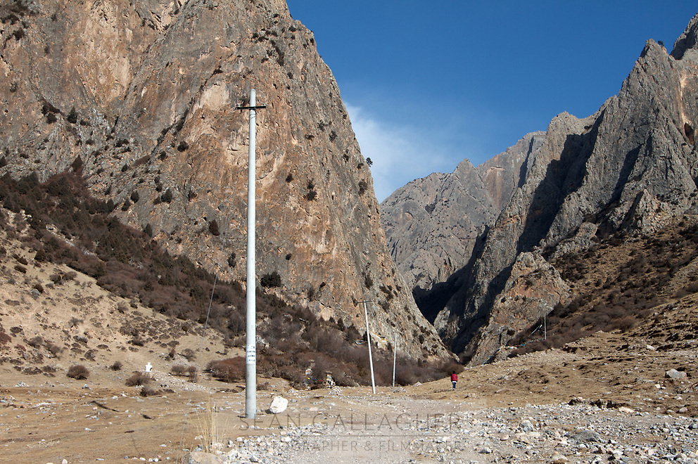 Telegraph poles lead into a valley high on the Qinghai-Tibetan Plateau. China