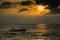 Fine Art Landscape Photograph, Sunset in Banderas Bay, Puerto Vallarta, Mexico. Fisherman in their small fishing boat sail by in as the warm golden rays of the sun cast highlights and textures on the ocean waters.