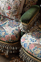 Fringes and tassels bedeck needlepoint covered chairs