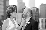 Playful candid of bride and groom on a terrace in NYC with buildings in the background.