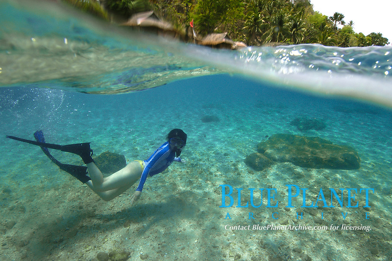 Split image of free diver next to sandy bottom and island huts, Verde Island, Philippines, Pacific Ocean