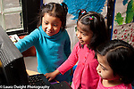 Education preschool 4 year olds three girls playing with computer