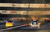 Nov 12, 2010; Pomona, CA, USA; NHRA funny car driver Tim Wilkerson (right) explodes an engine alongside Bob Bode during qualifying for the Auto Club Finals at Auto Club Raceway at Pomona. Mandatory Credit: Mark J. Rebilas-