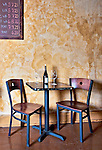 Table and Chairs in Wine Shop, with wine bottle and two glasses.  Old room in European style.