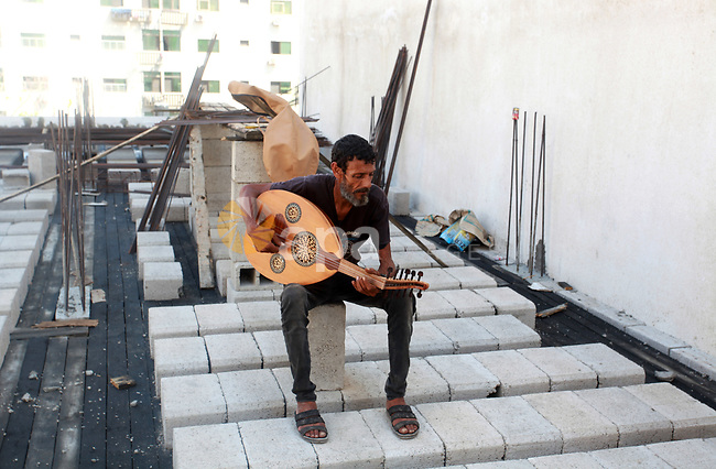 """Palestinian refugee, Kamal Abu Ghabin, 57, plays the lute known in Arabic as an """"Oud"""", during his rest, in Gaza city, on August 8, 2021. Abu Ghabin works as a blacksmith and has been playing the oud since his childhood. He plays the oud with his neighbors and friends every day. Photo by Omar Ashtawy"""