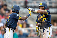 Michigan Wolverines designated hitter Jordan Nwogu (42) is greeted by teammate Christian Bullock (5) after scoring against the Florida State Seminoles during the NCAA College World Series on June 17, 2019 at TD Ameritrade Park in Omaha, Nebraska. Michigan defeated Florida State 2-0. (Andrew Woolley/Four Seam Images)
