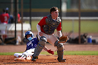 Catcher Cory Filley (6) waits for a throw as Yahir Acevedo (1) slides home safely during the Perfect Game National Underclass East Showcase on January 23, 2021 at Baseball City in St. Petersburg, Florida.  (Mike Janes/Four Seam Images)