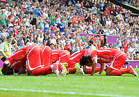 July 26, 2012..Hamdan Al Kamali (8) and rest of the team kiss the ground after scoring a goal. UAE vs Uruguay Football match during 2012 Olympic Games at Old Trafford in Manchester, England. Uruguay defeat United Arab Emirates 2-1...