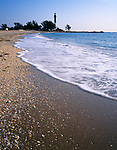 Broward County, FL  <br /> Sea shells cover the shoreline of Pompano Beach with Hillsboro Inlet Lighthouse (1906) in the distance