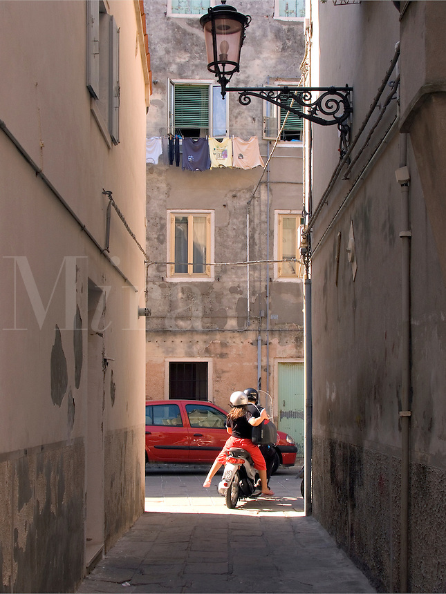 Two people riding motor scooter down narrow passageway between residential buildings in Chioggia Ital