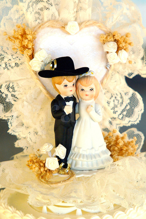 A bride and groom cowboy wedding cake topper is on top of a white wedding cake.