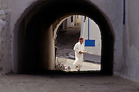 Tunisia, Sidi Bou Said.  Tunisian Man in Traditional Clothing Carrying a Tray of Eggs.