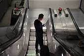 Man with a suitcase checks his mobile phone on a Westminster tube station escalator.