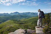 Zealand Notch  - A hiker takes in the view of the Pemigewasset Wilderness from the summit of Zeacliff during the summer months. This view point is along the Appalachian Trail in the White Mountains, New Hampshire. Much of this forest was logged during the East Branch & Lincoln Railroad era, which was a logging railroad in operation from 1893-1948.