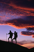 Hikers in silhouette under sunset sky and clouds.