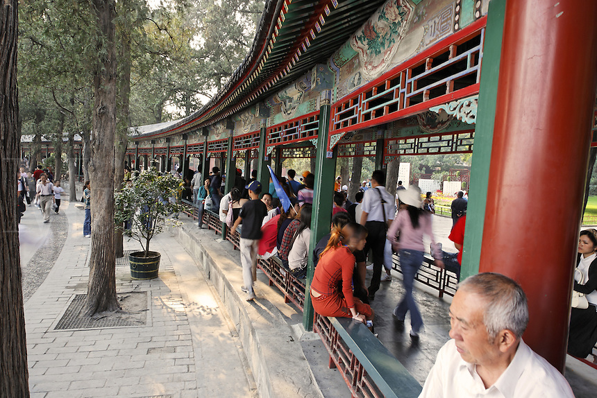 Summer Palace visitors sitting and walking along The Long Corridor, Beijing, China, Asia