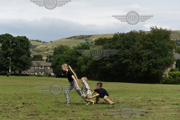 Irish Traveller Georgina McCarthy plays with her little brother Jimmy-Tom and cousin David, in a field in Halifax where the family were staying for a week in their mobile home.